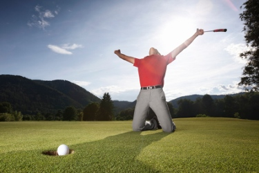 Successful golf player on green.